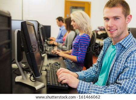 Side view of young students using computers in the computer room - stock photo