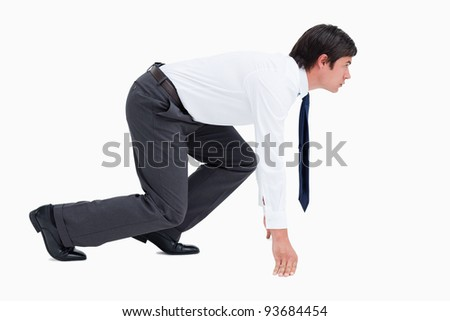 Side view of young tradesman in sprinting position against a white background - stock photo