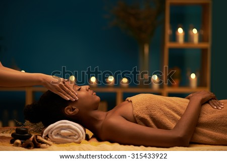 Side view of young woman enjoying massage in luxury spa resort - stock photo