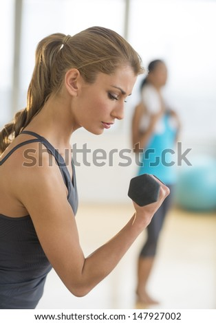 Side view of young woman lifting dumbbell at health club - stock photo