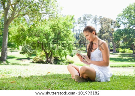 Side view of young woman on the lawn with her tablet computer - stock photo