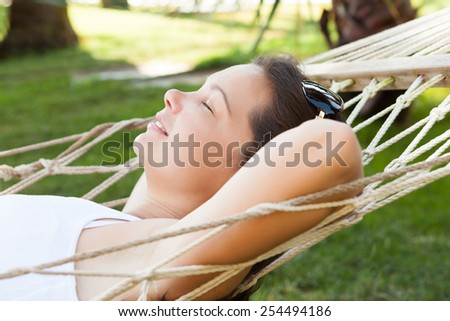 Side view of young woman resting in hammock at park - stock photo