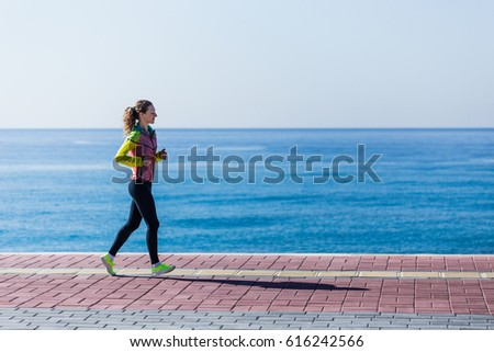 Side view of young woman running and wearing gym clothing with black tights and yellow sport shoes with sea on background