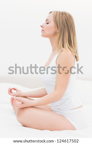 Side view of young woman sitting in lotus position in bed at home