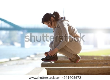 Side view of young woman tying shoe lace before run - stock photo