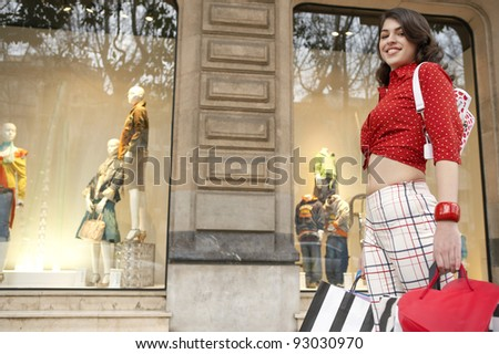 Side view of young woman walking by shop window, holding shopping bags in her hand. - stock photo