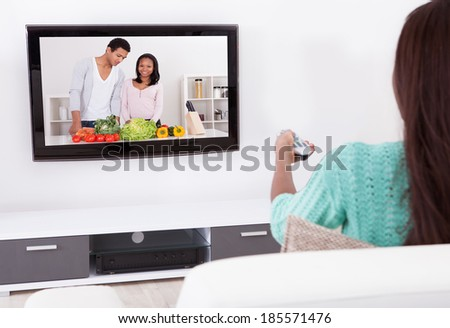 Side view of young woman watching TV in living room - stock photo