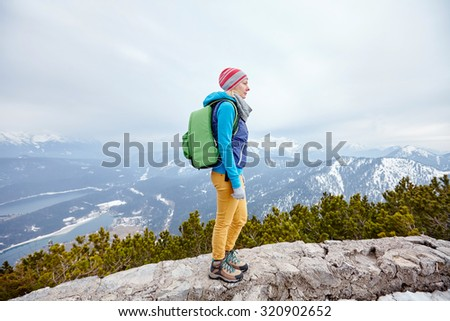 Side view of young woman wearing pink hat, blue jacket, green backpack, yellow pants and hiking boots standing against winter mountain valley - adventure concept - stock photo