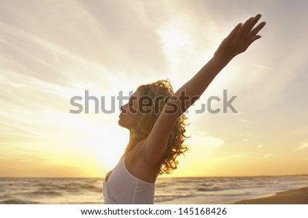 Side view of young woman with hands raised meditating at beach - stock photo