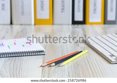 Side view on the working place of designer. Light wooden desk with color pencils, notepad with marked handwriting, computer keyboard and line of folders on the background. - stock photo