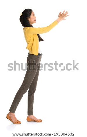 Side view or profile of an Asian girl arms up like holding something, full length standing isolated on white background. - stock photo