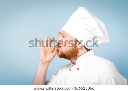 Side view photo of positive young male chef in white uniform. Head-cook gesturing perfectly cooked food and standing against grey background - stock photo