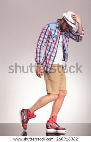 Side view picture of a casual man walking on studio background holding his hand on his hat while looking down. - stock photo