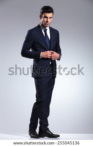 Side view picture of a handsome business man closing his jacket while looking away from the camera. - stock photo