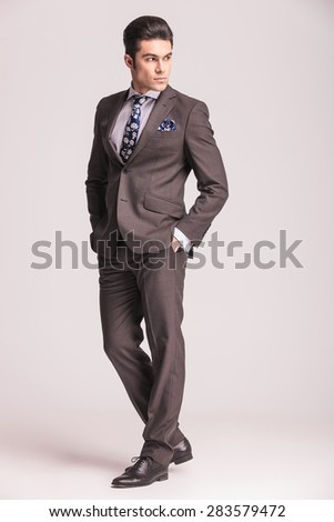 Side view picture of a young business man holding his hands in pockets while looking back. - stock photo