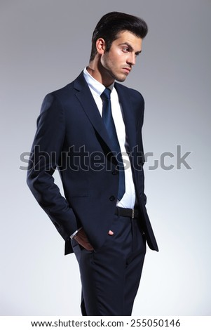 Side view picture of a young business man looking away from the camera while holding his hands in pockets.