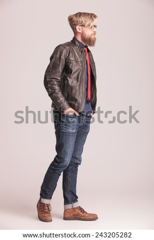 Side view picture of a young casual man walking with his hands in pockets. - stock photo