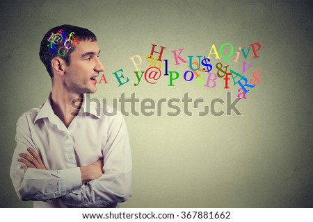 Side view portrait man talking with alphabet letters in his head and coming out of open mouth isolated on gray wall background. Human face expressions, emotions. Communication, intelligence concept - stock photo
