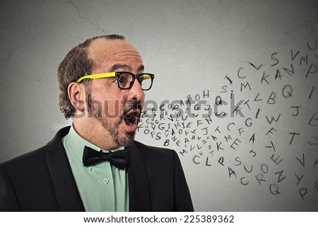 Side view portrait middle aged business man talking with alphabet letters coming out of open mouth isolated grey wall background. Human face expression emotion perception. Communication concept - stock photo