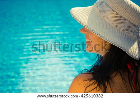 Side view portrait of a beautiful young female wearing sun hat. Swimming pool blue water surface in the background. Enjoying summer vacation concept.   - stock photo