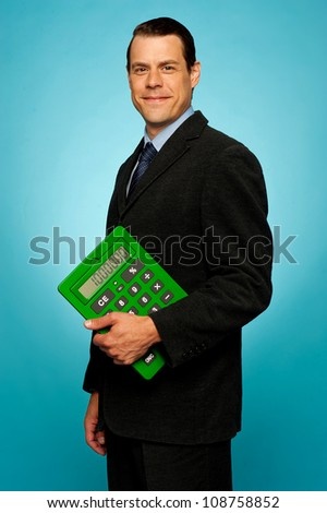 Side view portrait of a businessman with green calculator isolated over gradient background - stock photo