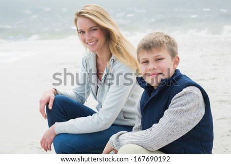 Side view portrait of a casual woman and son relaxing at the beach - stock photo