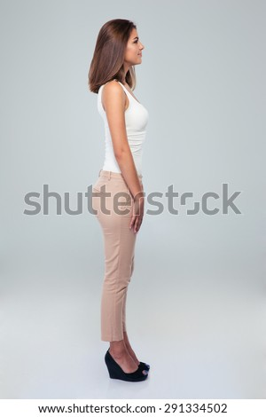 Side view portrait of a casual woman standing over gray background - stock photo