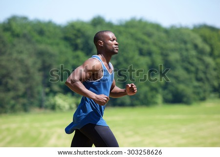 Side view portrait of a fit exercising man running outside - stock photo