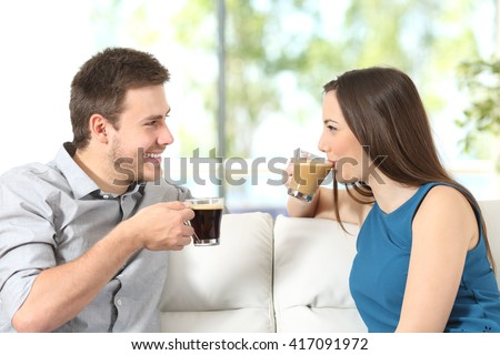 Side view portrait of a happy couple looking each other talking and drinking coffee sitting on a sofa at home with a window in the background