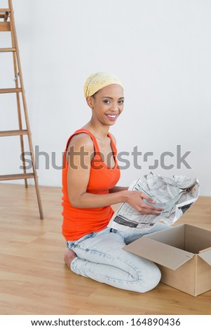 Side view portrait of a happy young woman moving in a new house and unwrapping boxes
