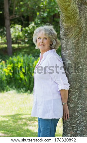 Side view portrait of a mature woman leaning against tree trunk in the park - stock photo