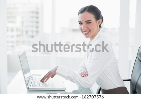 Side view portrait of a smiling businesswoman using laptop at desk in a bright office - stock photo