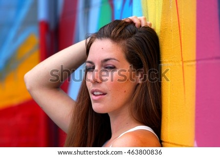 Side view portrait of a woman with colorful wall in the background.