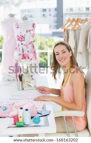 Side view portrait of a young female fashion designer working on fabrics in the studio - stock photo