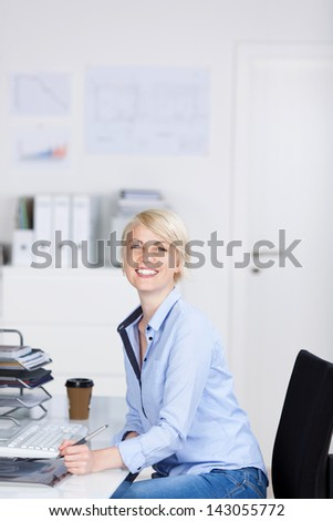 Side view portrait of a young laughing businesswoman sitting at office desk - stock photo