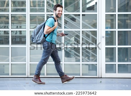 Side view portrait of a young man walking on sidewalk with mobile phone and bag - stock photo