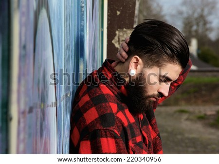 Side view portrait of a young man with beard and piercings outdoors - stock photo