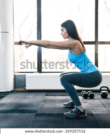 Side view portrait of a young woman doing squats at fitness gym - stock photo