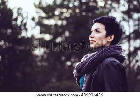 Side view portrait of an attractive young woman outdoor - stock photo