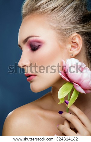 Side view portrait of attractive blonde woman with sensitive makeup holding peony near her face, on blue background, close up. Fashion photo.  - stock photo