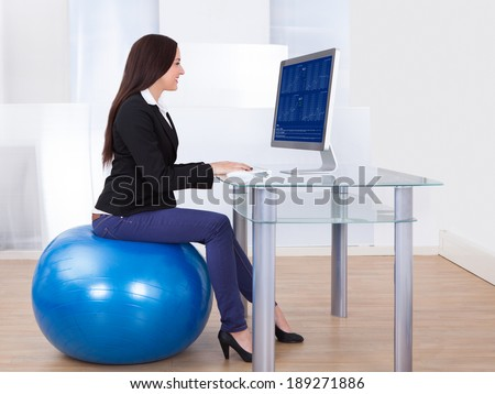 Side view portrait of businesswoman using computer while sitting on pilates ball in office - stock photo