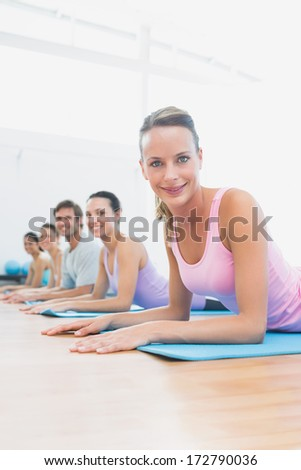 Side view portrait of fit class exercising in row at fitness studio
