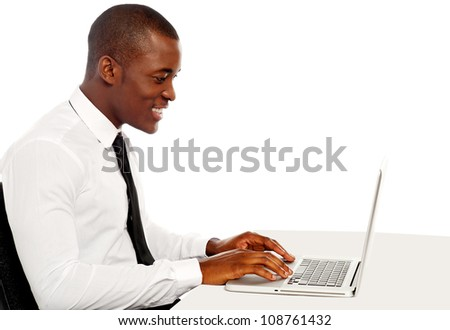 Side view portrait of handsome business executive working on laptop