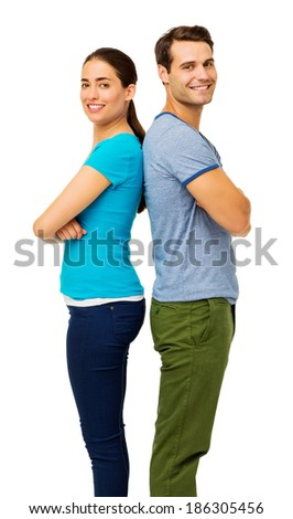 Side view portrait of happy couple with arms crossed standing over white background. Vertical shot. - stock photo