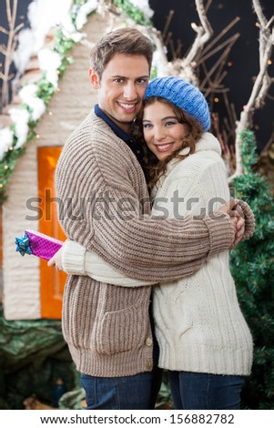 Side view portrait of happy young couple embracing at Christmas store - stock photo