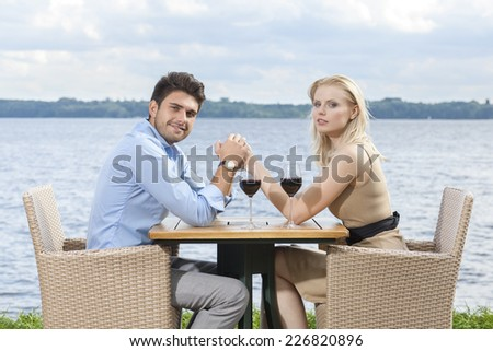 Side view portrait of young couple holding hands at outdoor restaurant by lake