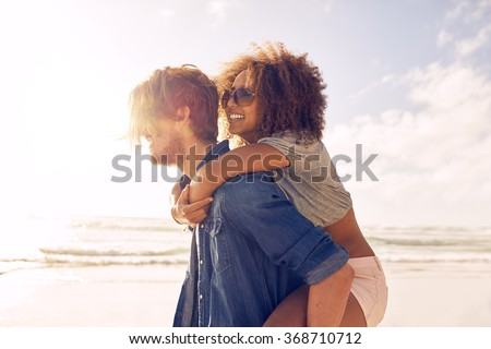 Side view portrait of young man carrying his girlfriend on his back at the beach. Boyfriends giving piggyback ride to his beautiful girlfriend at seashore. - stock photo