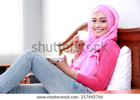 side view portrait of young muslim woman holding a cup of tea - stock photo