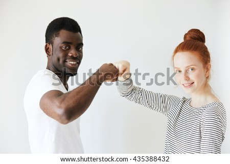 Side view portrait of youngster salutating each other with bumping fists. Caucaisan redhead girl smiling at camera with her African American friend or coworker, showing positive emotions and peace. - stock photo