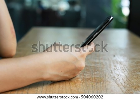 Side view shot of women's hands holding smart phone in coffee cafe, Hipster girl using mobile phone during coffee break. (Selective Focus)